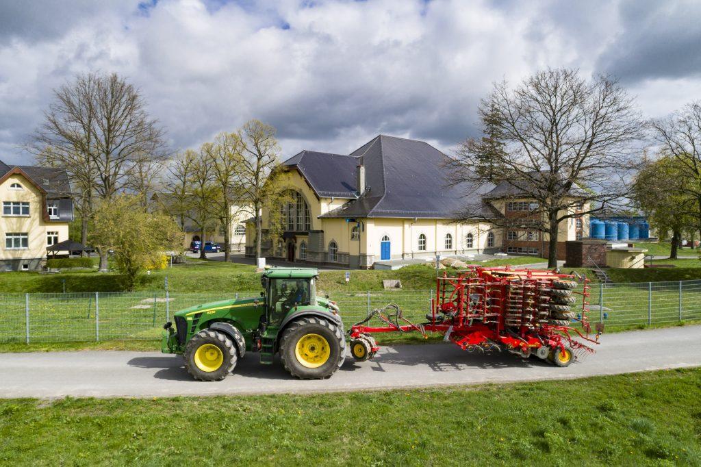 Das Bild zeigt das Wasserwerk Canitz, eines von vier Großwasserwerken der Leipziger Wasserwerke. Im Vordergrund kreuzt ein Traktor den Weg. Trinkwasserförderung und Ökolandbau gehen hier zum Schutz der Ressourcen Hand in Hand.