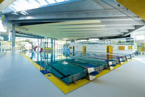 Die Schwimmhalle verfügt über ein 25-Meter-Schwimmbecken mit sechs Bahnen. Die äußerliche Industrie-Architektur setzt sich auch im Inneren fort.