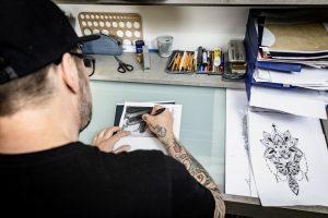 Schulterblick auf die Vorzeichnung eines Tattoos