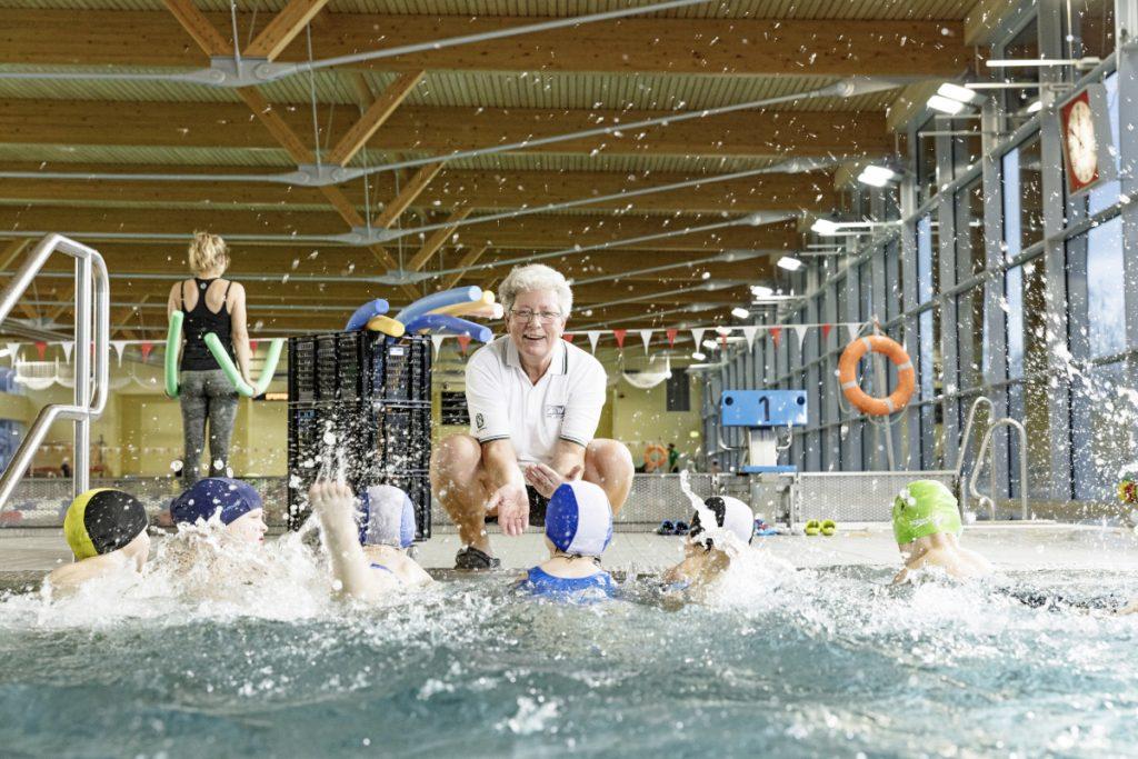 Die Schwimmlehrerin am Beckenrand mit wasserbegeisterten Schülern.