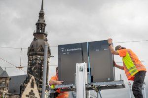 Zwei Techniker installieren auf der Haltestelle Goerdelerring einen Anzeiger