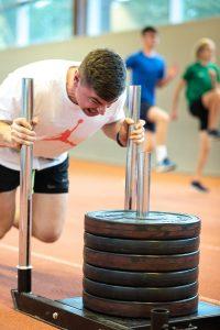 David Storl schiebt als Kraftübung einen Schlitten mit Gewichten.